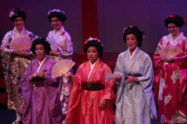 On the left in purple playing Peep Bo in the Mikado